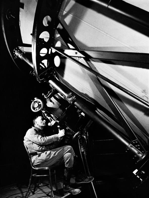 American astronomer Edwin Hubble looks through the eyepiece of the 100-inch telescope at the Mount Wilson Observatory in Los Angeles, 1937. In 1929, Hubble proposed that the more distant a galaxy is, the faster it appears to be receding from us, a concept that has become known as Hubble's law.
