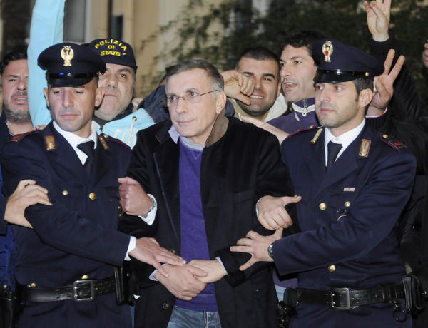 Italian policemen escort fugitive mobster Michele Zagaria, center, at the police headquarters in Naples.