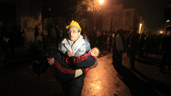 A demonstrator in Cairo runs with an injured child during clashes with security forces last month. A growing number of children are participating in anti-government protests, and their numbers are rising among the casualties.