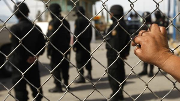 A relative of an inmate observes Mexican police behind the security fence after a riot inside Apodaca prison near Monterrey. At least 44 inmates were killed during Sunday's riot, and about 30 alleged members of the drug cartel Los Zetas were rushed out of the prison.