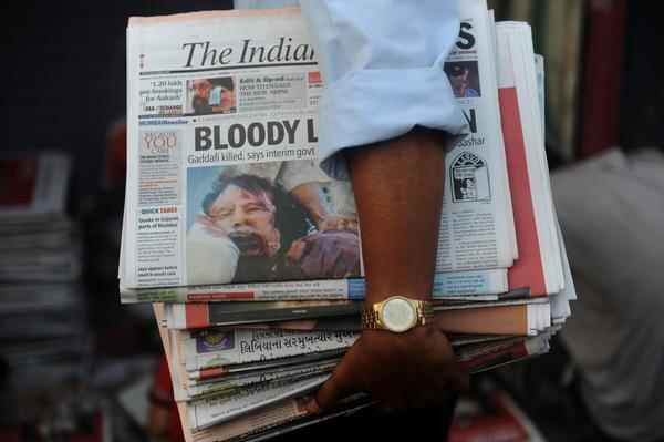 A vendor distributes papers with the news of Moammar Gadhafi's death in Mumbai on Friday.