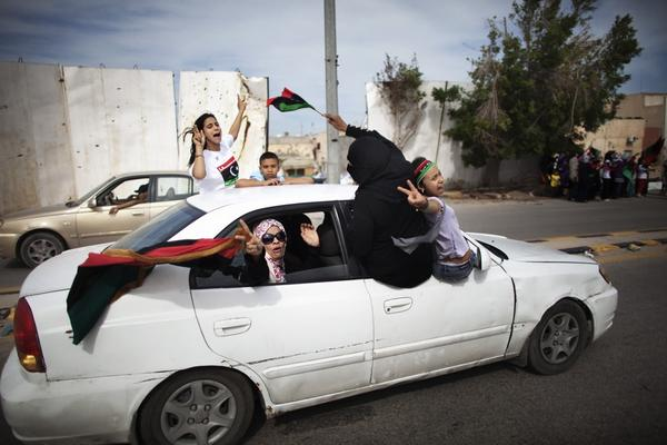 Libyan women and children wave NTC flags as they celebrate in the streets of Tripoli following news of Moammar Gadhafi's death.