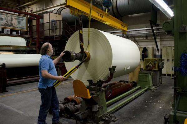 Rewinder operator John Danylieko moves a finished roll of currency paper from the paper machine. The roll will be cut into three narrower rolls before being cut into sheets.