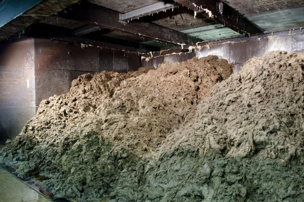 Several tons of linen fibers drain and cool down after having been cooked in the rotary digester, a giant steel ball.