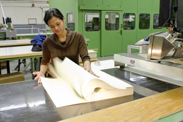 Marites Wilbur performs a final inspection on a ream of 32-note currency paper sheets.