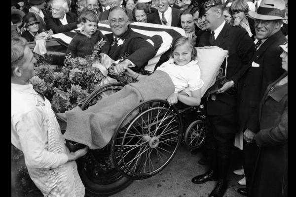 The vast majority of polio victims are children, but it can also strike adults. Franklin D. Roosevelt contracted polio in 1921 at age 39. Here, two men lift a little girl in a wheelchair so that Roosevelt can greet her from his vehicle during his first presidential campaign.