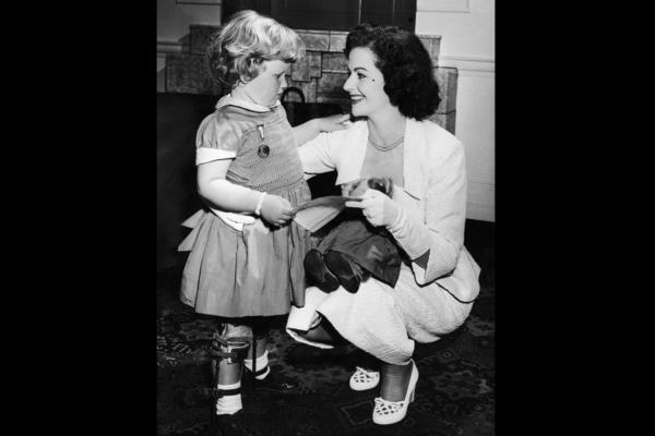 Many celebrities and actresses helped to promote the fight against polio. In this image from 1953, the British actress Margaret Lockwood speaks with a young polio survivor, 4-year-old Mary Burton, as they buy stamps to support polio research and treatment.