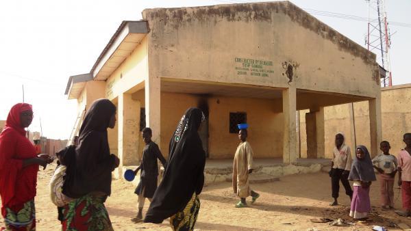 Women walk past the polio vaccine dispensary in Kano, Nigeria, where gunmen killed female health workers last Friday.