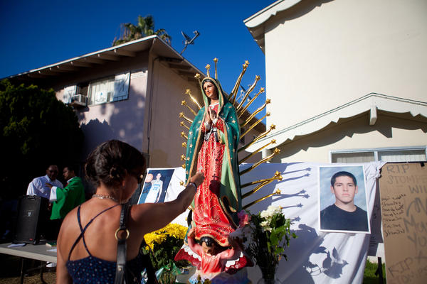 A local resident prays at a memorial for Manuel Diaz, on July 29, 2012 in Anaheim, Calif.
