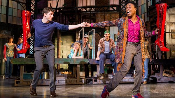 Struggling shoe-factory owner Charlie (Stark Sands, left) is inspired by drag queen Lola (Billy Porter) to make high-quality high-heeled boots for men who perform as women in the Broadway adaptation of the cult film <em>Kinky Boots</em>.