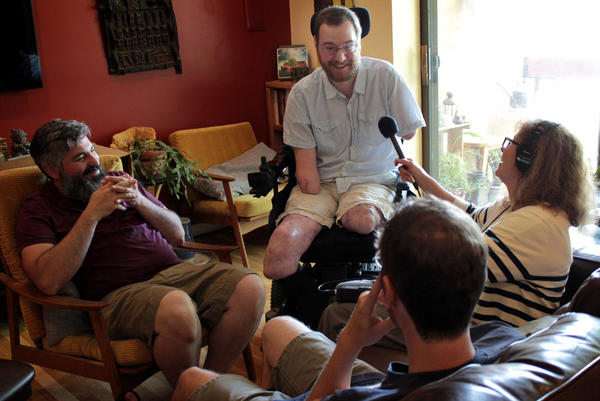 Robin Young (right) interviews Will Lautzenheiser for this piece. At left is his partner Angel Gonzalez. On the couch is twin Tom Lautzenheiser. (Sam Fields/Here & Now)