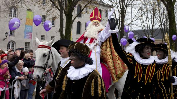 """People line the road to greet Sinterklaas, the Dutch version of Santa Claus, and his """"Swarte Piet"""" (Black Pete) sidekicks in Amsterdam on Nov. 17, 2013. In the past few years, Black Pete has come under fire. Some say it's a beloved tradition that should remain; others say it is a racist stereotype."""
