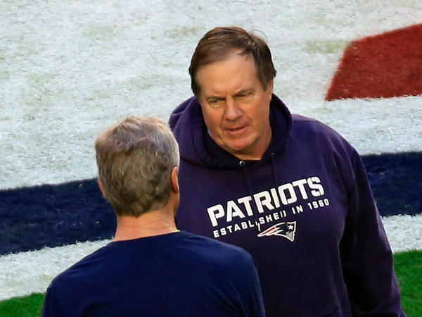 Patriots head coach Bill Belichick shakes hands with Seahawks coach Pete Carroll.