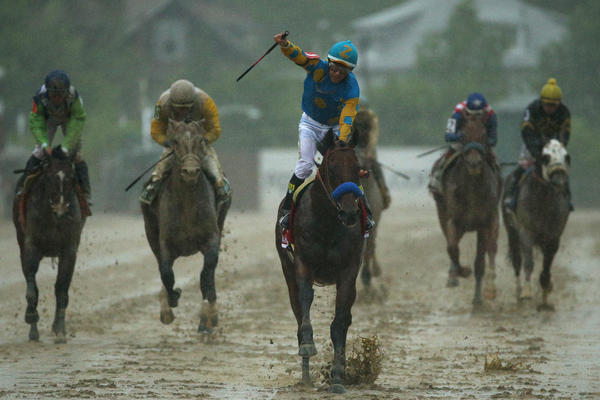 American Pharoah, ridden by Victor Espinoza, crosses the soggy finish line to win the 140th running of the Preakness Stakes at Pimlico Race Course on Saturday.
