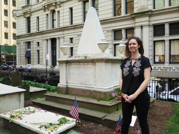 Trinity Church archivist Anne Petrimoulx stands in front of Alexander Hamilton's grave in New York City. The site has seen a surge in visitors following the popular Broadway musical, <em>Hamilton</em>.