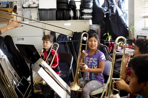 Esmeralda Martinez, center, demonstrates good trombone posture. Her practice room is an office and storage room by day which requires the kids to squeeze in between filing cabinets, folding chairs and stacked instruments.