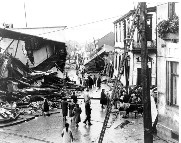 Residents of Valdivia, Chile, look over wrecked buildings on May 31, 1960.
