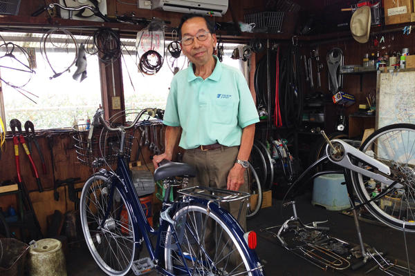 """Nenosuke Yamamoto, 80, stands in the shed where he repairs bicycles in Tokyo. """"I feel that if I keep on working, I might not age as much,"""" he says. """"I might not have dementia or other sorts of aging issues."""""""