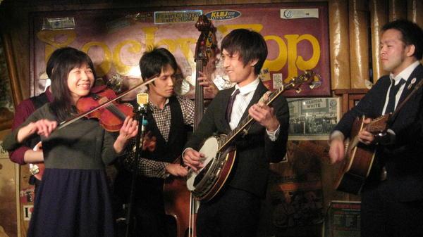 Bluegrass Police is a popular act at the Tokyo bluegrass club Rocky Top. From left to right are mandolin player Satoshi Hoshikawa (obscured), fiddler Yuuko Wakabayashi, bassist Tomonari Hiraizumi, banjo player Tatsuya Kuwahara and guitarist and vocalist Mitsutaka Sometaya.