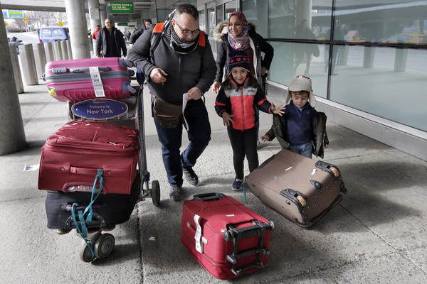Munther Alaskry, accompanied by his wife, Hiba; son, Hassan; and daughter, Dima, gather their luggage as they leave JFK International Airport in New York on Feb. 3. Alaskry and his family arrived after the Trump administration reversed course and said he and other interpreters who had supported the U.S. military could come to America.