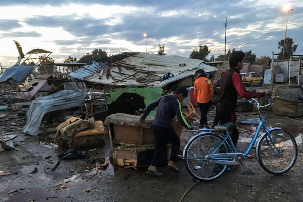 Two Iraqi children push a bicycle past the scene of a massive car bomb blast on Thursday that killed dozens of people in southern Baghdad.