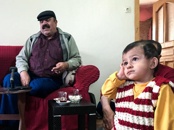 As Mistefa Bedevi sings, 1-year-old Mirhat mimics performance poses, holding his hand over his ear.