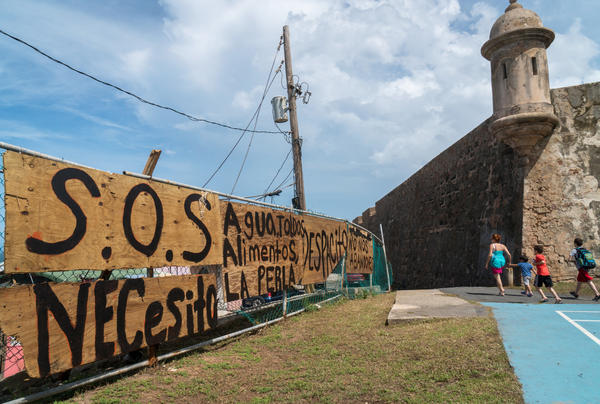 """Residents set up signs asking for help in the basketball court of La Perla neighborhood in Old San Juan, Puerto Rico after Hurricane Maria's destruction. La Perla is where the """"Despacito"""" video was filmed."""