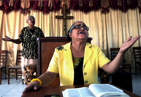 Co-pastor Leticia Gonzalez preaches as her fellow pastor Nereido Gonzalez (left) stands at the altar.