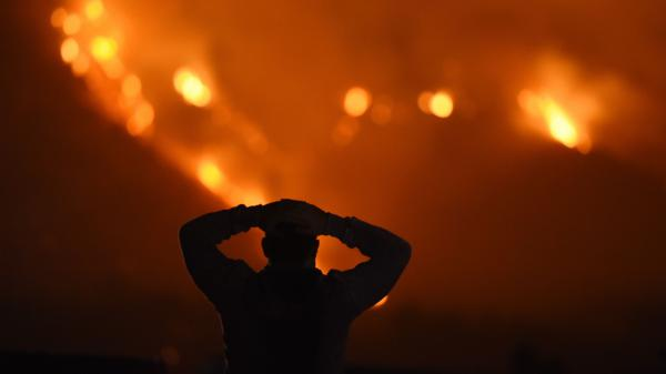 A man watches the Thomas Fire in the hills above Carpinteria, California.