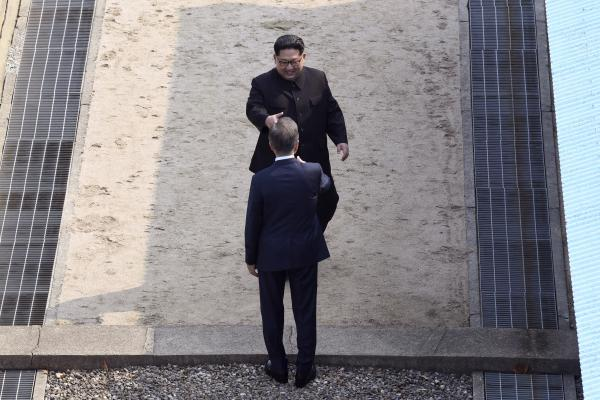 Kim approaches to shake hands with Moon at the border village of Panmunjom in the Demilitarized Zone, South Korea, on Friday.