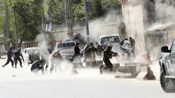 Security forces run from the site of a suicide attack after a second bombing in Kabul, Afghanistan, on Monday.