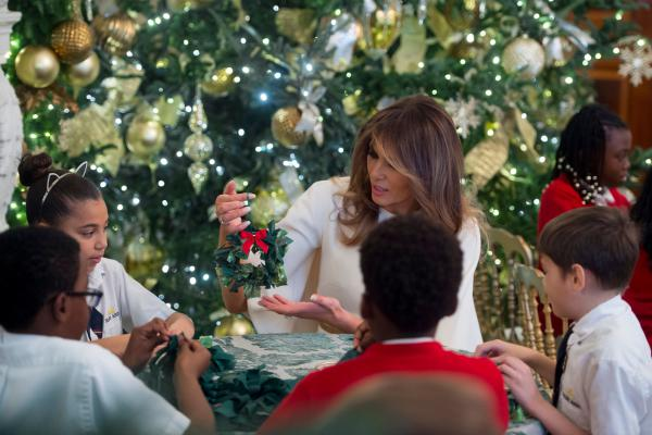 Melania Trump makes Christmas decorations with children in the State Dining Room as she tours holiday decorations at the White House on November 27, 2017.