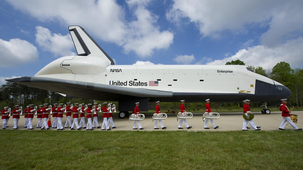 U.S. Marine Drum and Bugle Corps and Color Guard march past the space shuttle Enterprise at the Steven F. Udvar-Hazy Center on April 19, 2012, in Chantilly, Va.