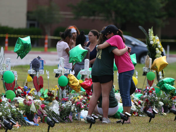 People mourn last week at a makeshift memorial in memory of the victims killed in a shooting at Santa Fe High School in Santa Fe, Texas. Students resumed classes at the school today.