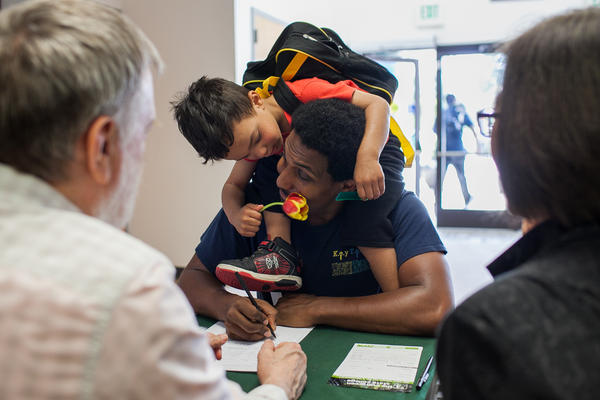 Nathan Powers, 3, offers his father, Adam Powers, a flower while he talks with campus representatives at the Spring Fair at Evergreen State College's Tacoma, Wash. campus on May 19. Powers, of Des Moines, Wash., works at a nonprofit and is considering going back to school.