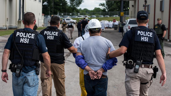 Special agents with Homeland Security Investigations, the investigative arm of U.S. Immigration and Customs Enforcement, lead a man away from Fresh Mark in Salem, Ohio, on Tuesday. The mass arrests were the result of the second such large-scale raid this month.