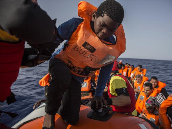 A child aboard a rubber dinghy off the Libyan coast is helped by rescuers aboard the Open Arms aid vessel.