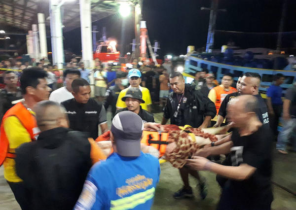 Thai rescue crews attend to passengers of a capsized tourist boat in rough seas at a port in Phuket on Thursday.