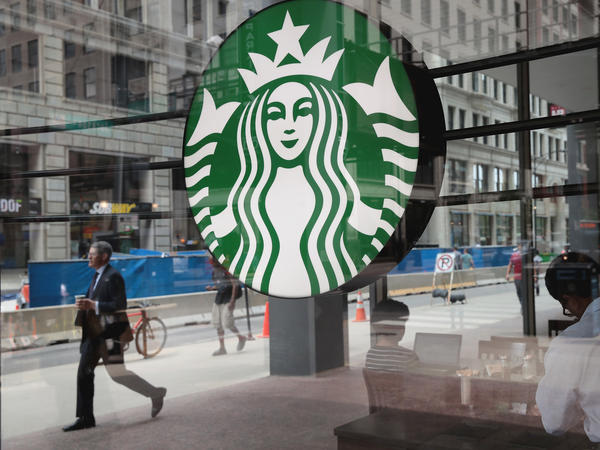 People walk by a Starbucks store in Chicago on May 29. Starbucks announced that it plans to remove plastic straws from its 28,000 stores worldwide by 2020.