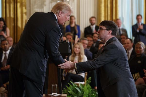 President Donald Trump shakes hands with acting Department of Veterans Affairs Secretary Robert Wilkie after announcing he will nominate him to lead the department during an event on prison reform in the East Room of the White House, Friday, May 18, 2018.
