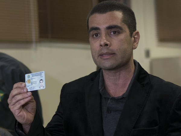 Brazilian surgeon Dr. Denis Cesar Barros Furtado shows his doctors license as he speaks to the media at the police department after his arrest in Rio de Janeiro, Brazil, on Thursday.