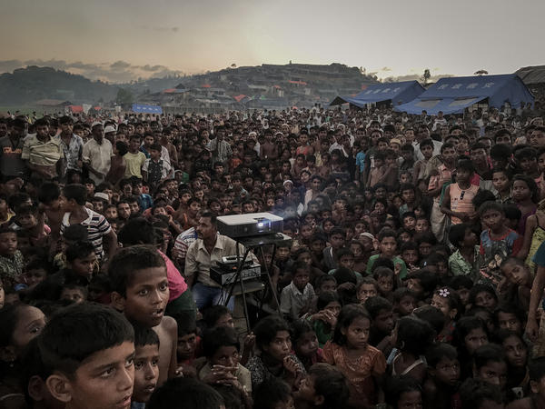 Rohingya refugees watch a film about health and sanitation in a camp in Bangladesh.