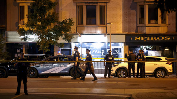 Police officers walk the scene in the Greektown neighborhood of Toronto on Sunday night. Police say a gunman opened fire on people in a restaurant. Three people are dead including the gunman, police reported.