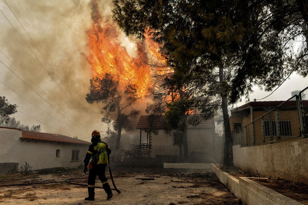 A firefighter tries to extinguish hotspots during a wildfire in Kineta on Monday.