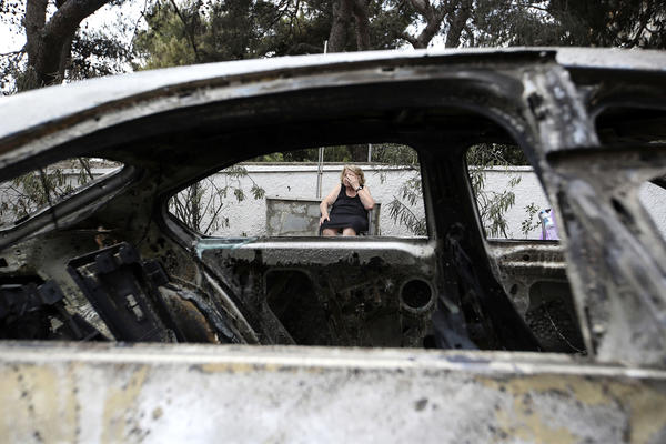 Asimina Psalti, 87, sits outside her burned house in the resort village of Mati on Tuesday.