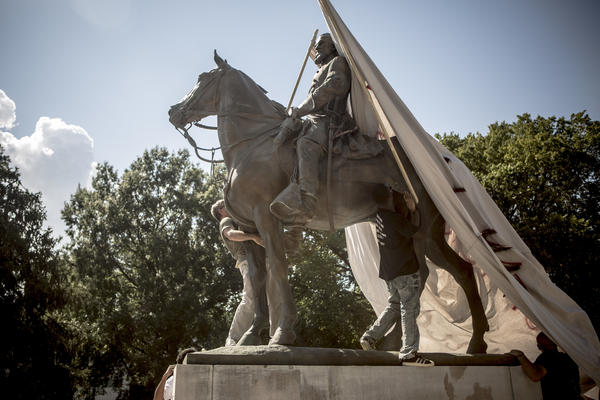 Protesters attempt to cover a statue of Ku Klux Klan leader Nathan Bedford Forrest at Health Sciences Park in Memphis, Tenn., in August 2017. The statue was removed in December.