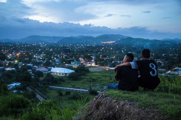 """Moises, 17, left, and Jaime look down on the patchwork of neighborhoods outside San Pedro Sula, a city in Honduras where gang rivalries play out. The violence is so bad that """"no one goes in"""" the neighborhoods, says photojournalist Tomas Ayuso. """"Food delivery trucks, ambulances don't want to go in because they're afraid something will happen."""""""