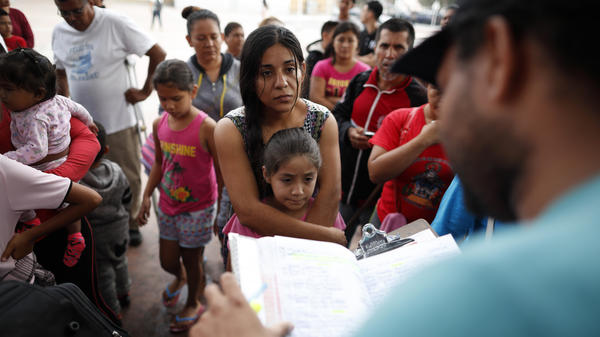A woman from the Mexican state of Michoacán who did not give her name stands with her daughter at the San Ysidro Port of Entry in Tijuana, Mexico, as names are read off a list of people who will cross into the United States to begin the process of applying for asylum.