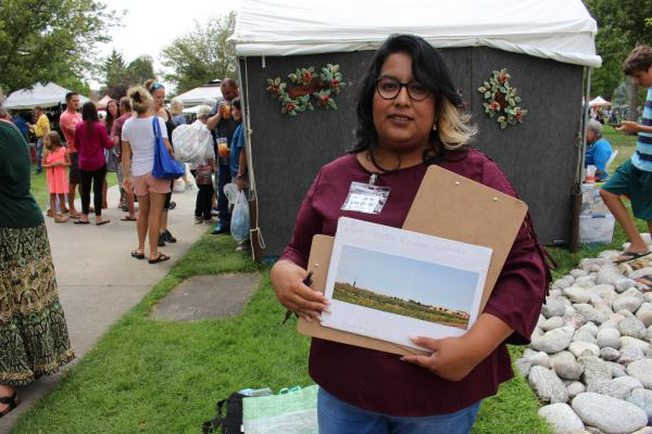 Patricia Nelson holds a clipboard and a photo of her son Diego's future school, Bella Romero Academy, in Greeley. The picture shows the proximity of a new oil rig to the building, a source of tension for many parents.