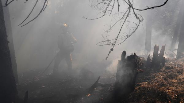 Firefighters deal with heavy smoke as they try to contain flames from the Carr Fire as it spreads toward the town of Douglas City near Redding, Calif.